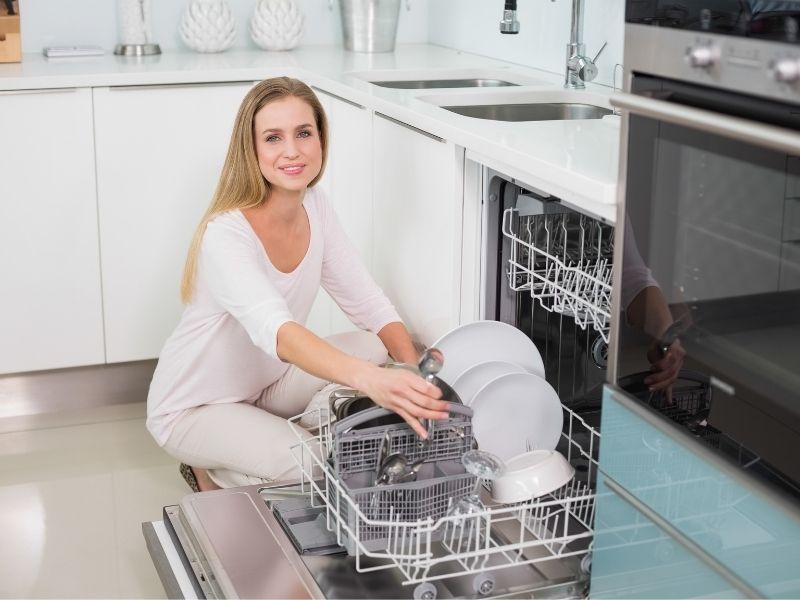 Žena stavlja suđe u perilicu posuđa Miele