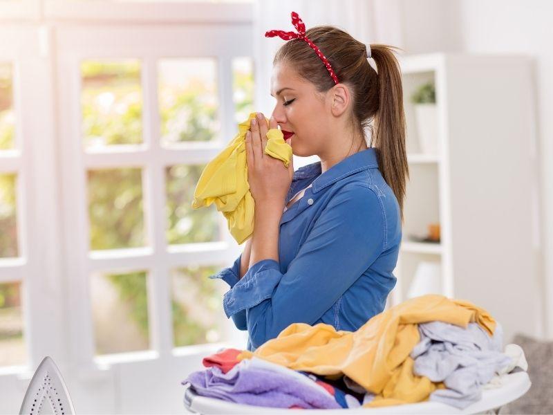 Mlada žena uživa u svježem rublju opranom pomoću Miele perilice rublja